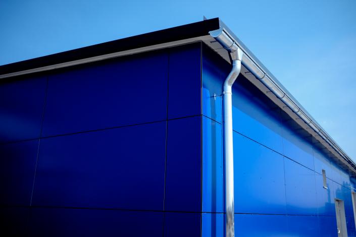 Blaue Aluverbund Fassade mit Fallrohr und Dachrinne